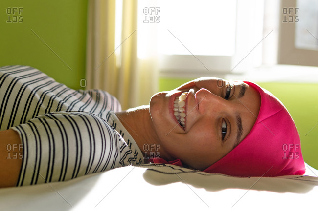 Side view of young female with cancer wearing headscarf resting on bed at home while looking at camera