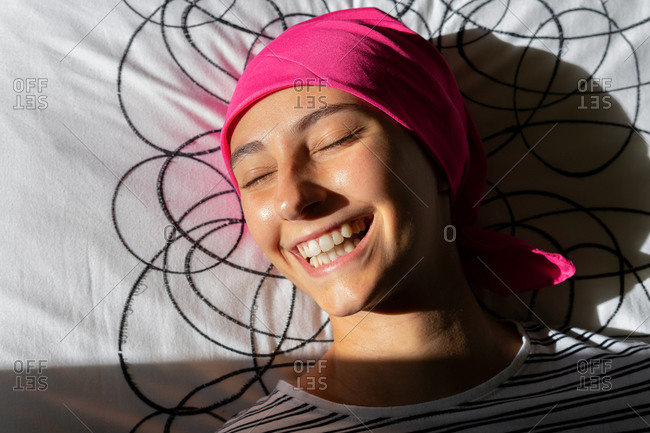 From above of young female with cancer wearing headscarf resting on bed at home