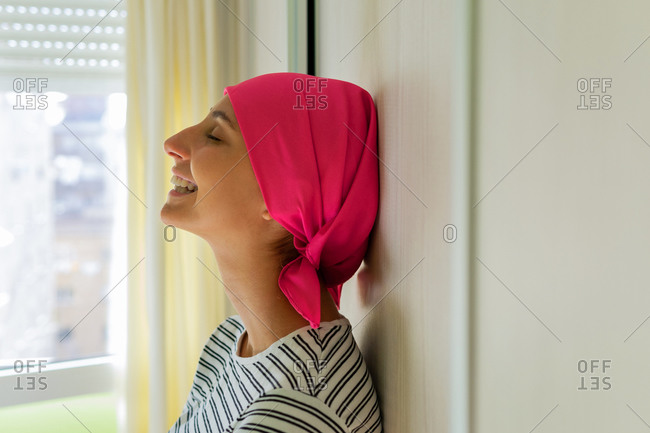 Young delighted female with cancer wearing headscarf standing in apartment