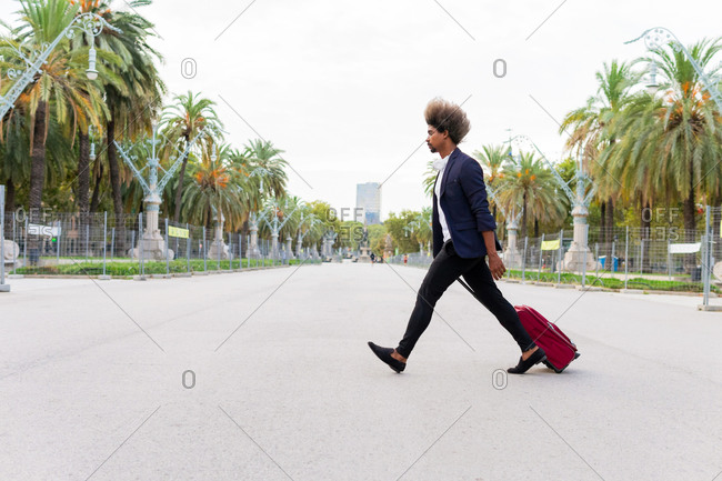 Side view of a young black man in a suit dragging a wheeled suitcase down the street on a tree-lined avenue