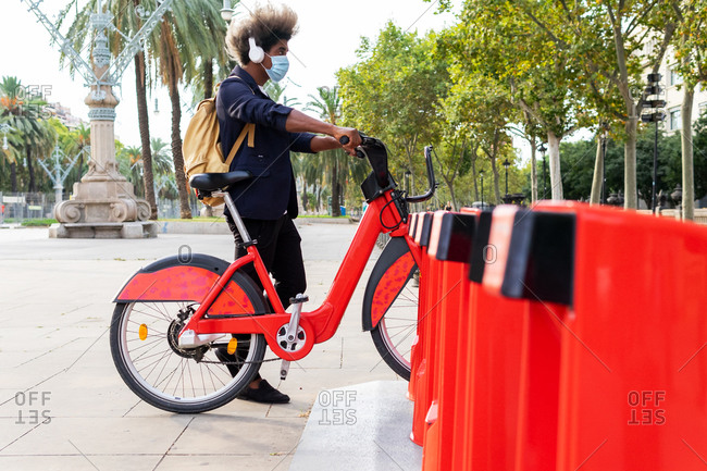 Young black man in a suit and mask listening to music while using a public bicycle on the street
