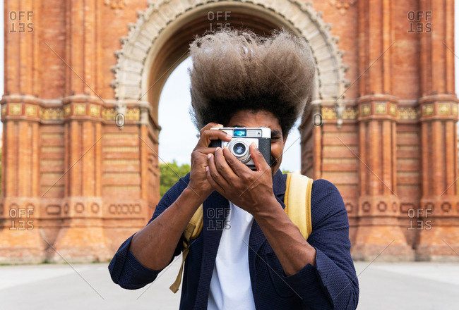 Black man taking a picture while facing the camera with a camera in Arch of Triumph Barcelona