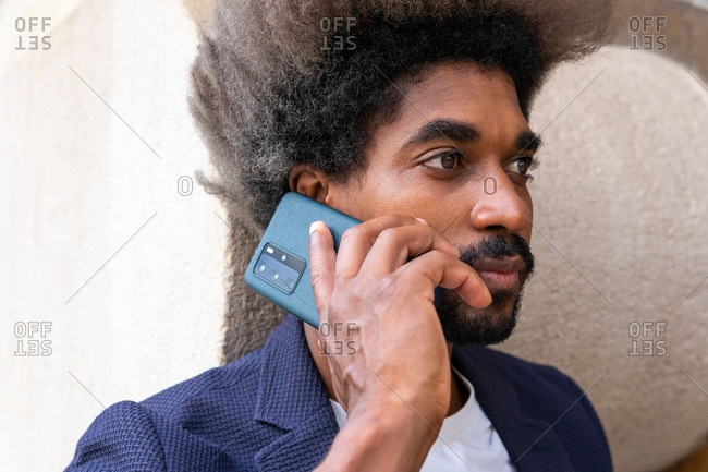 Side view portrait of an african man in suit using his mobile phone in front of a wooden wall