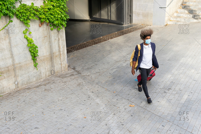 Top view of black man in a suit walking with suitcase on the street