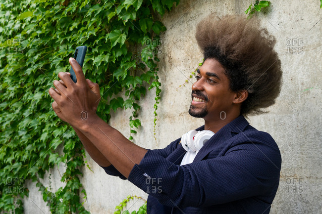 Young black man in a suit standing on the street taking selfie on the mobile phone