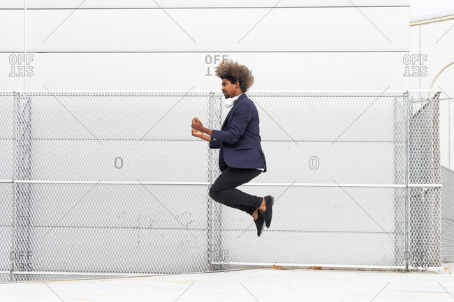 Side view of well dressed ethnic male entrepreneur jumping near urban building looking away