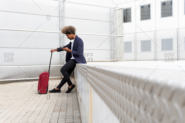 Side view of black man in a suit with a wireless helmet around his neck sitting outdoors using his mobile phone and holding a suitcase