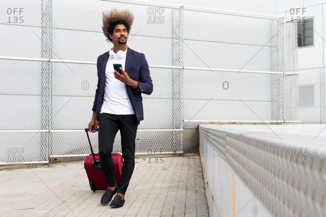 Black man in a suit with a wireless headphones around his neck and a suitcase walking while using the mobile outdoors