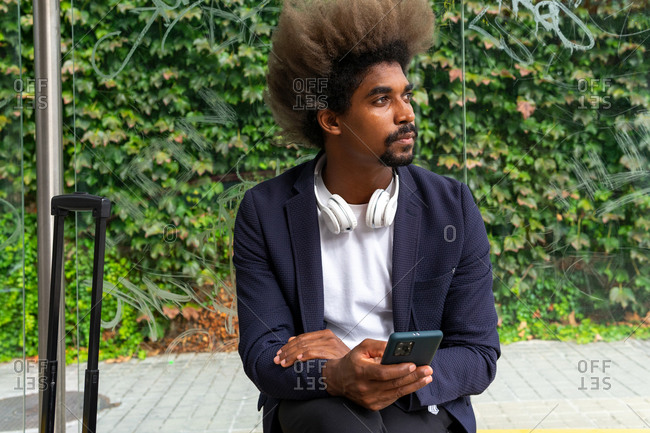 African man with afro hair sitting on a bench outside with headphones around his neck and a suitcase while using his mobile