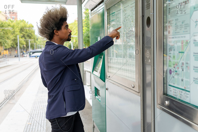 Side view of black man with afro hair standing and pointing on a map of public transport at a tram station