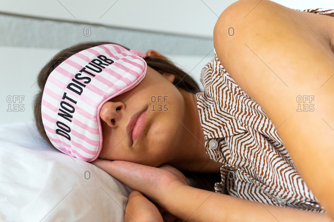Peaceful female sleeping in eye mask in soft bed in bright modern apartment