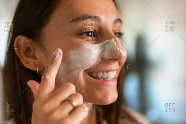 Smiling female in domestic clothes looking in mirror and applying moisturizing mask on face while doing beauty routine procedure
