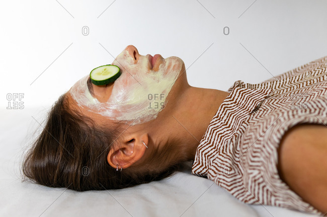 Closeup of relaxed female with hydrating facial mask and slices of fresh cucumber on eyes enjoying beauty treatment in spa salon