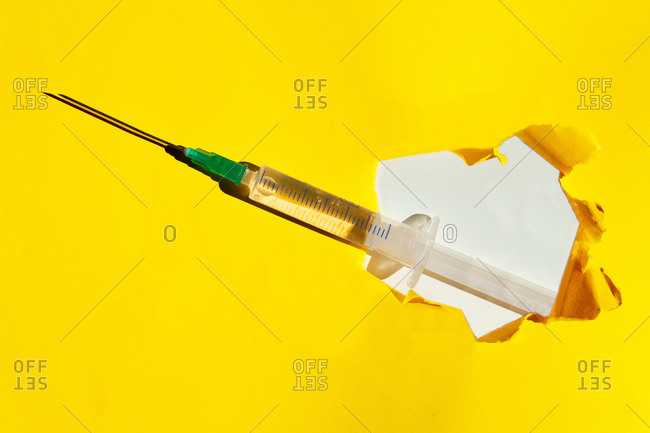 Top view of syringe with vaccine placed on torn yellow paper background in studio