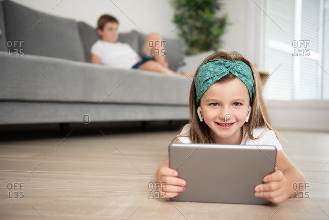 Little girl with true wireless earphones lying down on the floor while entertained using tablet during weekend