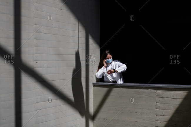 Female doctor in white uniform and medical mask checking time on wristwatch while talking on mobile phone during break from work on hospital terrace