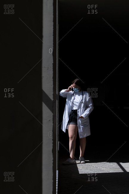 Full length of unrecognizable female doctor in white medical coat and protective mask standing in sunlight near wall and having phone conversation during break in clinic