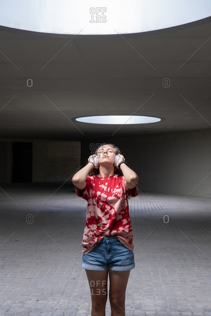 Hipster female student in casual outfit touching headphones while listening to song and relaxing in illuminated hallway of contemporary building
