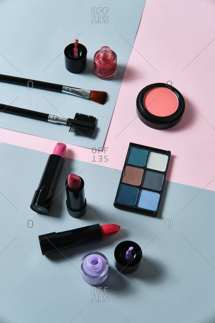 High angle of assorted decorative cosmetics and applicators arranged on two colored background in studio
