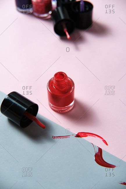 High angle of stylish red nail lacquer smeared on table in modern studio