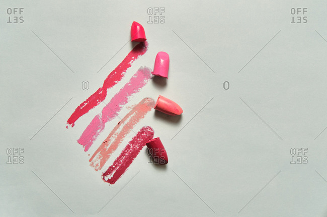 High angle of lipstick bullets of various colors smudged on white surface in beauty salon