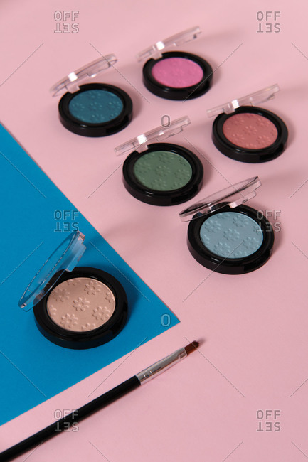 Top view of set of trendy colorful eyeshadows and brush arranged on two colored background in studio