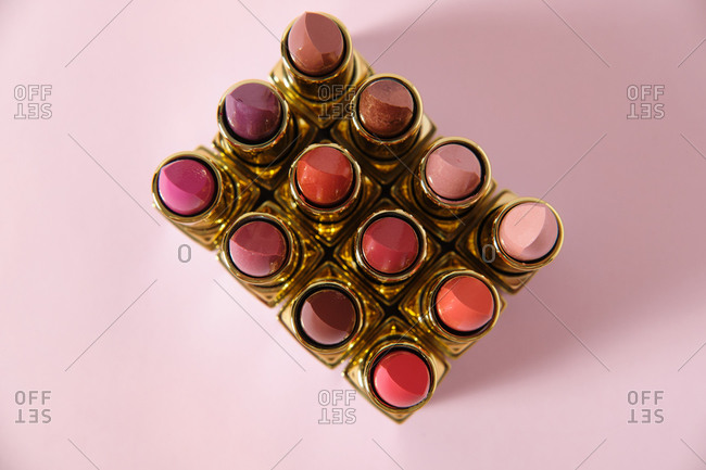 From above of collection of assorted matte lipsticks arranged in rows on pink background in studio