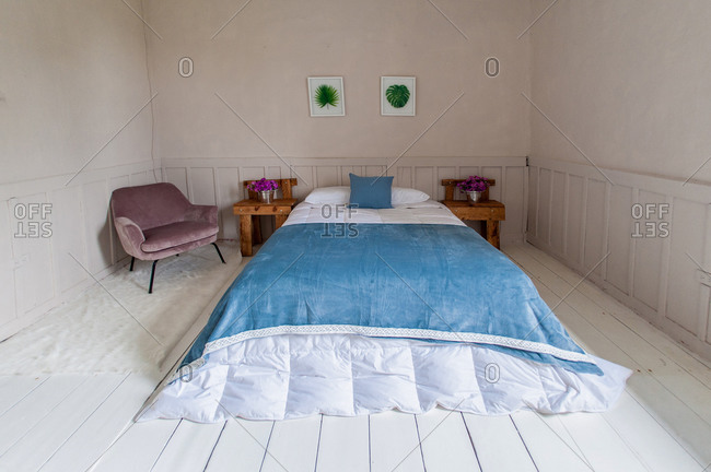Minimal interior of hotel room with cozy bed and bedside tables on wooden floor