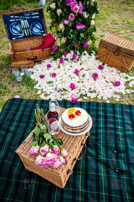 High angle of sweet cake and bottle of wine arranged with wineglasses and bouquet of flowers on wicker basket on green lawn for summer picnic