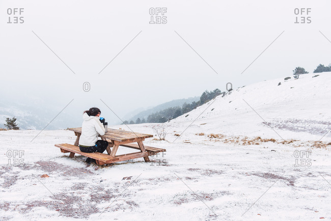 Side view of anonymous traveler relaxing on wooden bench and drinking hot tea in thermos while enjoying amazing view of mountains in winter in Pyrenees