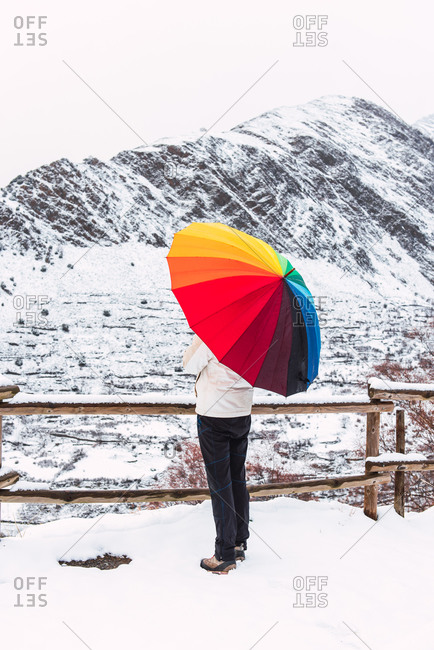 Side view of anonymous person standing under colorful umbrella and enjoying amazing view of Pyrenees mountain ridge covered with snow in winter