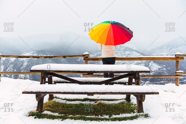Back view of anonymous person standing under colorful umbrella and enjoying amazing view of Pyrenees mountain ridge covered with snow in winter