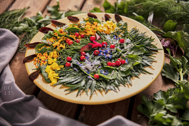 From above of composition of ripe greenery and flower petals arranged on wooden table