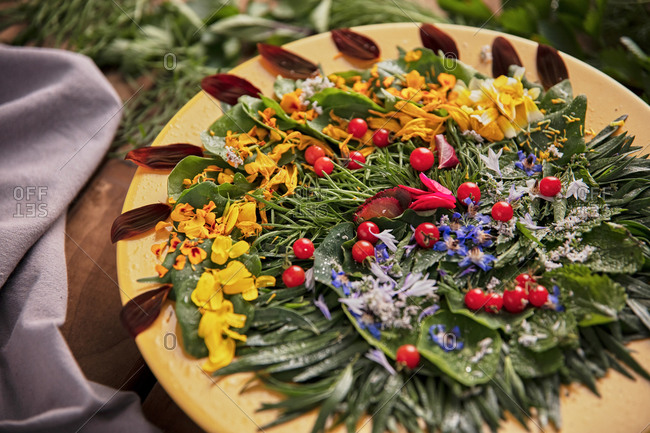 Top view of composition of ripe greenery and flower petals arranged on wooden table
