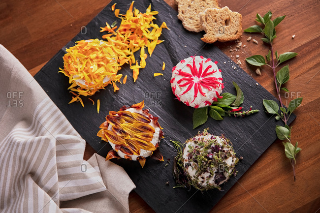 Delicious round shaped curd decorated with edible flower petals and placed on slate board on table in kitchen