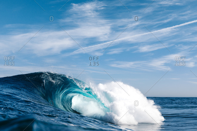 Powerful blue breaking ocean waves with white foam