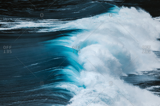 From above view of powerful blue breaking ocean waves with white foam