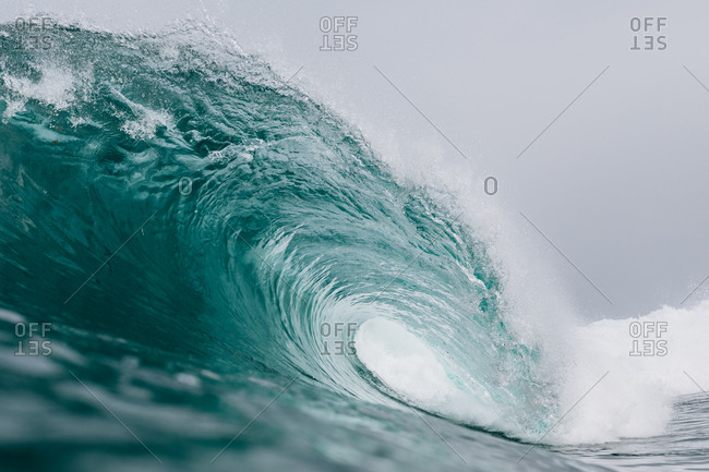 Powerful turquoise breaking ocean waves with white foam
