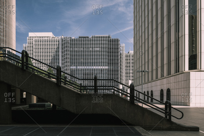 Stone staircase in city on background of tall contemporary skyscrapers on sunny day