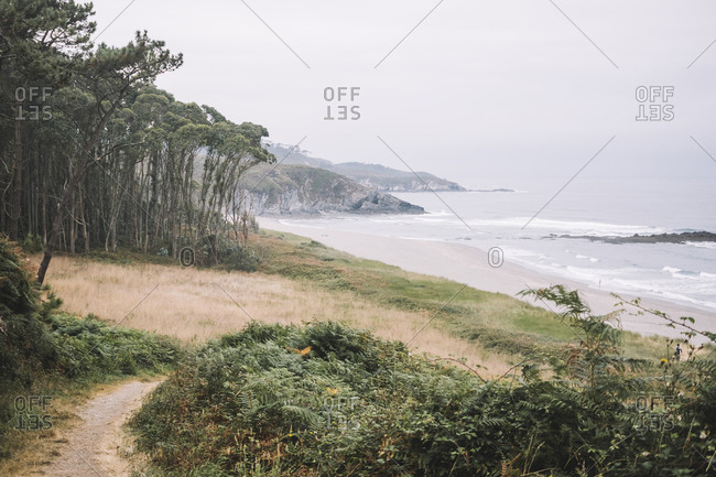 Gloomy summer landscape of Frejulfe Beach in Asturias with waving foamy sea and green plants on hilly shore against overcast sky