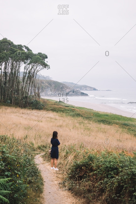 Back view of unrecognizable lonely female in black dress standing on narrow trail leading through grassy hill towards sea in cloudy summer day in Asturias in Spain