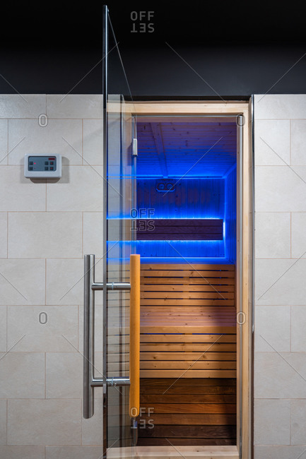 Wooden interior of traditional spacious sauna with benches illuminated by lamp with ultraviolet light