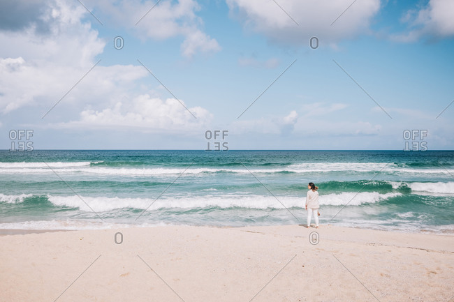 Full body back view of unrecognizable female traveler standing barefoot on empty sandy beach near waving sea and enjoying fresh breeze during summer holidays in Spain