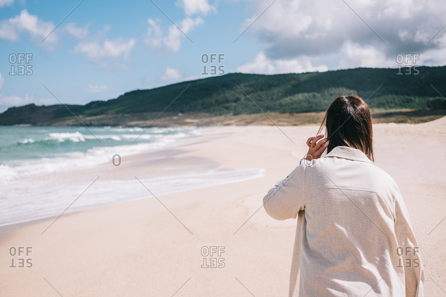 Back view of unrecognizable female traveler standing barefoot on empty sandy beach near waving sea and enjoying fresh breeze during summer holidays in Spain