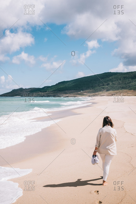 Full body back view of unrecognizable female traveler walking barefoot on empty sandy beach near waving sea and enjoying fresh breeze during summer holidays in Spain
