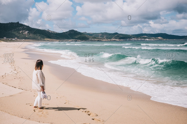 Full body side view of unrecognizable female traveler standing barefoot on empty sandy beach near waving sea and enjoying fresh breeze during summer holidays in Spain