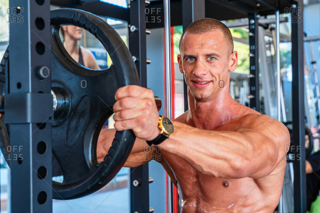 Cheerful muscular male athlete preparing barbell plates for workout in fitness center while looking at camera
