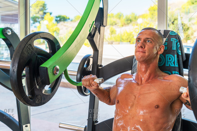 Athletic shirtless sportsman pumping muscles on chest press machine during intense training in bright gym