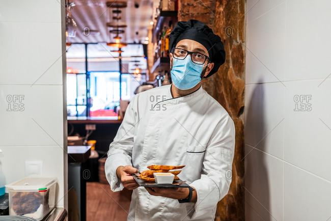 Serious male chef in uniform and medical mask standing with delicious snacks on slate board in cafe and looking at camera