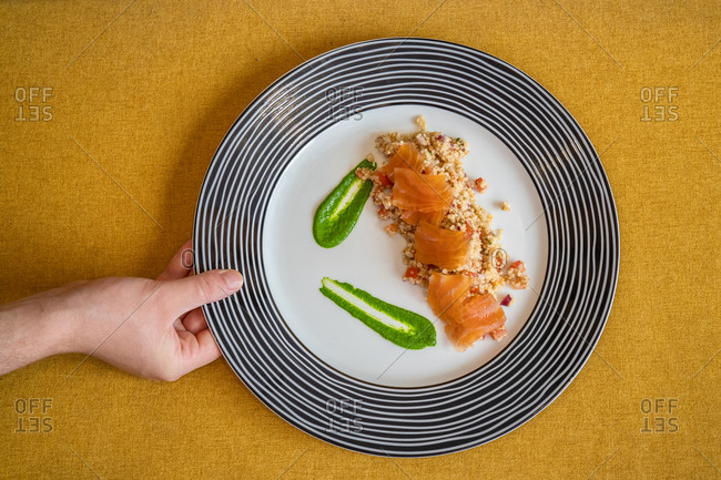 Top view of anonymous person with plate of rice garnished with slices of salmon and guacamole sauce served on table in cafe